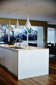 Central island with sink and pendant lamps in modern kitchen
