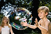 Two children trying to catch a bubble