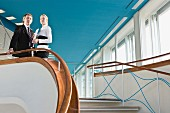 Two business people standing at the top of a staircase