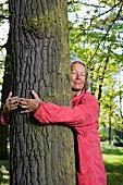 An older woman hugging a tree