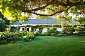 Weite Rasenfläche vor langgezogenem kanadischen Landhaus