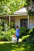 Woman and dog in summery garden in front of white, weatherboard country house with veranda