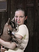 A girl holding a kid goat