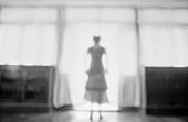 Frau sthet hinter luftigem Vorhang