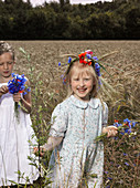 Two girls in a wheat field with bunches of wildflowers