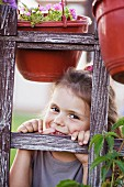 A young smiling girl looking through a trellis