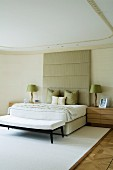 Double bed with upholstered, tall, pastel grey headboard in elegant bedroom with stucco ceiling and white rug