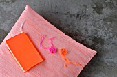 Hand-crafted book cover in neon orange and crocheted flowers on cushion