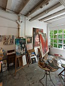 Artist's studio - painting utensils on side table and pictures on easels in rustic ambiance