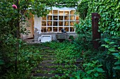 Overgrown path made from sleepers in garden outside house with lattice window and weathered facade