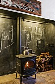 Wood-burning stove in front of blackboard wall with chalk drawings and stacked firewood in rustic ambiance