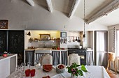 Dining table with white tablecloth opposite kitchen counter in rustic dining area with wood-beamed ceiling