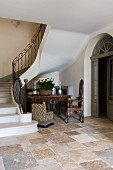 Foot of staircase with wrought iron balustrade, stone floor and antique furniture in historical, French country house