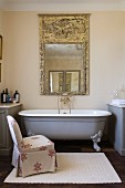Nostalgic bathtub and loose-covered easy chair below artistic mirror on wall