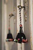 Cord tassel in dark brown and pastel colours hanging from vintage key