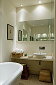 Narrow bathroom with mirror, dramatic lighting, floating washstand and counter-top basin
