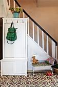 Garderobenschrank aus weiss lackiertem Holz vor Treppenaufgang in rustikalem Hausflur mit gemustertem Fliesenboden