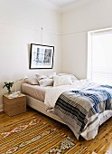 Ethnic rug next to bed with striped bedspread in simple bedroom