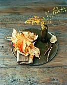 Autumnal arrangement of leaves & vase of twigs