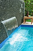 Waterfall emerging from screen of stacked stones next to pool