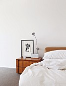 Wooden bedside cabinet and wall-mounted lamp next to bed with white bed linen