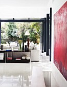 Glossy, white tiled floor in modern interior with open sideboard behind sofa opposite open, folding terrace doors with view into garden