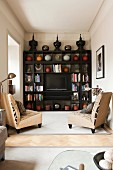 Pale armchairs in front of ceramic vases and TV on dark wooden shelving in living room