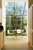 View through open-plan kitchen area of dining table with modern swivel chairs in glazed conservatory with view into garden