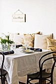 French-style table setting with embroidered tablecloth and Thonet chairs; printed, hessian scatter cushions and sign on wall in background