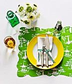Besteck und Serviette mit Geschenkband verschnürt auf Teller mit gelbem Rand und Set aus bedrucktem Geschenkpapier mit Wellenrand
