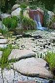 Pond with aquatic plants, large stone slabs and waterfall