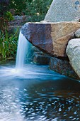Waterfall flowing over boulder