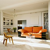 Sofa with orange upholstery and set of plexiglass coffee tables in living room; wooden designer chair in foreground