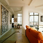 Sofa with orange upholstery in front of modern artwork on wall in living room of penthouse apartment with floor-to-ceiling windows