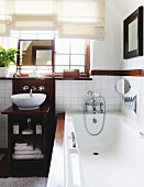 Bathtub with vintage tap fittings next to washstand with wooden cabinet below window with Roman blinds