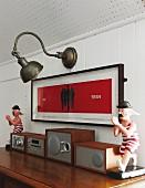 Stereoanlage vor gerahmtem Bild und Vintage Wandbeleuchtung an weisser Holzverkleidung