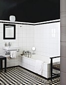 Black and white bathroom with chequered floor, sink, bathtub, white wall tiles and black-painted upper walls