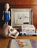 Still-life arrangement of fake skull, stacked books, painted wooden figurine and picture on table top