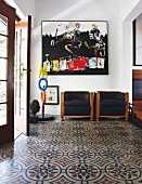 Foyer with patterned tiled floor and armchairs with black covers against wall below modern artwork