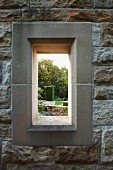 Window opening in stone wall with view of garden