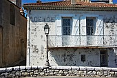 Mediterranean house with weathered facade and white, wrought iron balcony behind street lamp on low stone wall