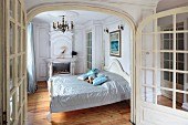 Open twin doors with view into traditional bedroom with shiny throw on French bed and fireplace in background
