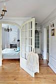 Open wing of double doors, view into bedroom in traditional apartment with rustic wooden floor