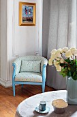 Blue-painted vintage armchair with pale fabric cover in corner of living room next to floor-length curtains on window; bouquet of white roses in foreground