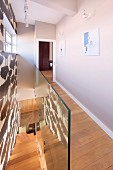 House with modern stairwell, narrow landing, wooden floor and glass balustrade