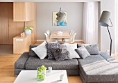 Grey sofa combination with scatter cushions and floodlight standard lamp in open-plan interior with dining area in background