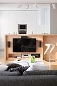 View over sofa to flatscreen TV mounted on wooden counter and white fitted cupboards with integrated kitchen appliances in background