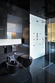 Schwarz gefliestes Designerbad mit schwarzen Sanitärobjekten, neben verglaster, bodenebener Dusche