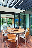 Modern, round outdoor table and chairs made from wooden slats on terrace with pergola