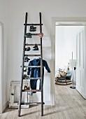 Alte Dachbodenleiter mit paarweise aufgehängten Kinderschuhen und Kinderoverall; Zimmerflucht in Wohnraum mit altem Schaukelstuhl